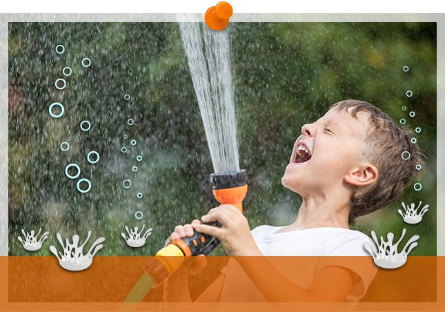 photo of a boy showering himself with a hose