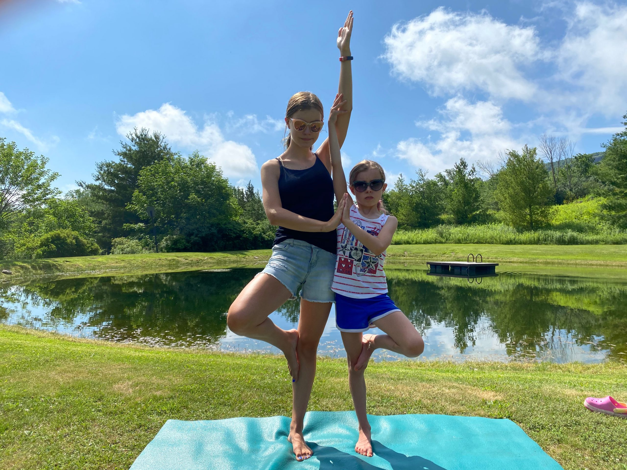 Two people stand in tree pose