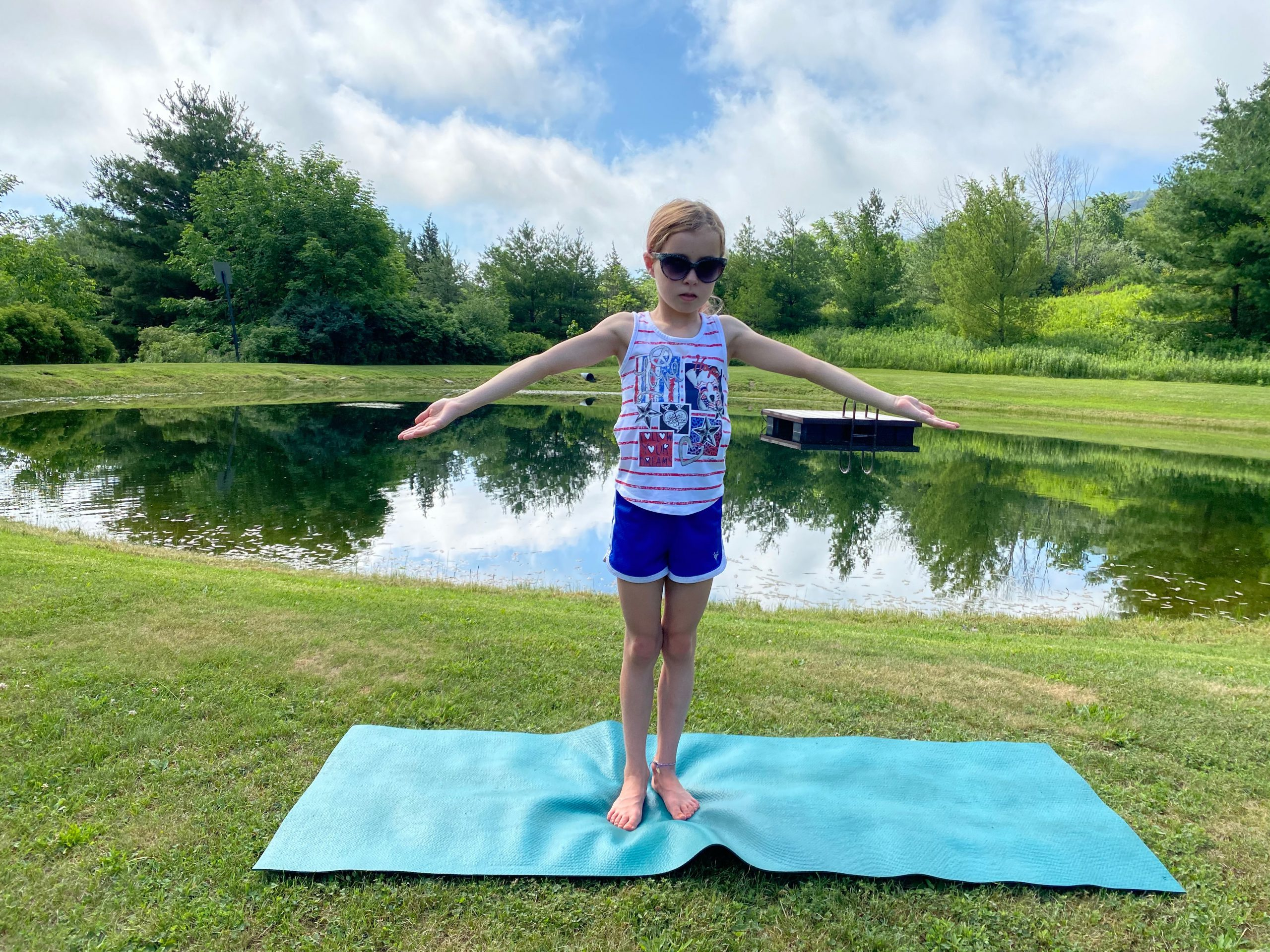 Child with arms partly raised in Sun Breath pose