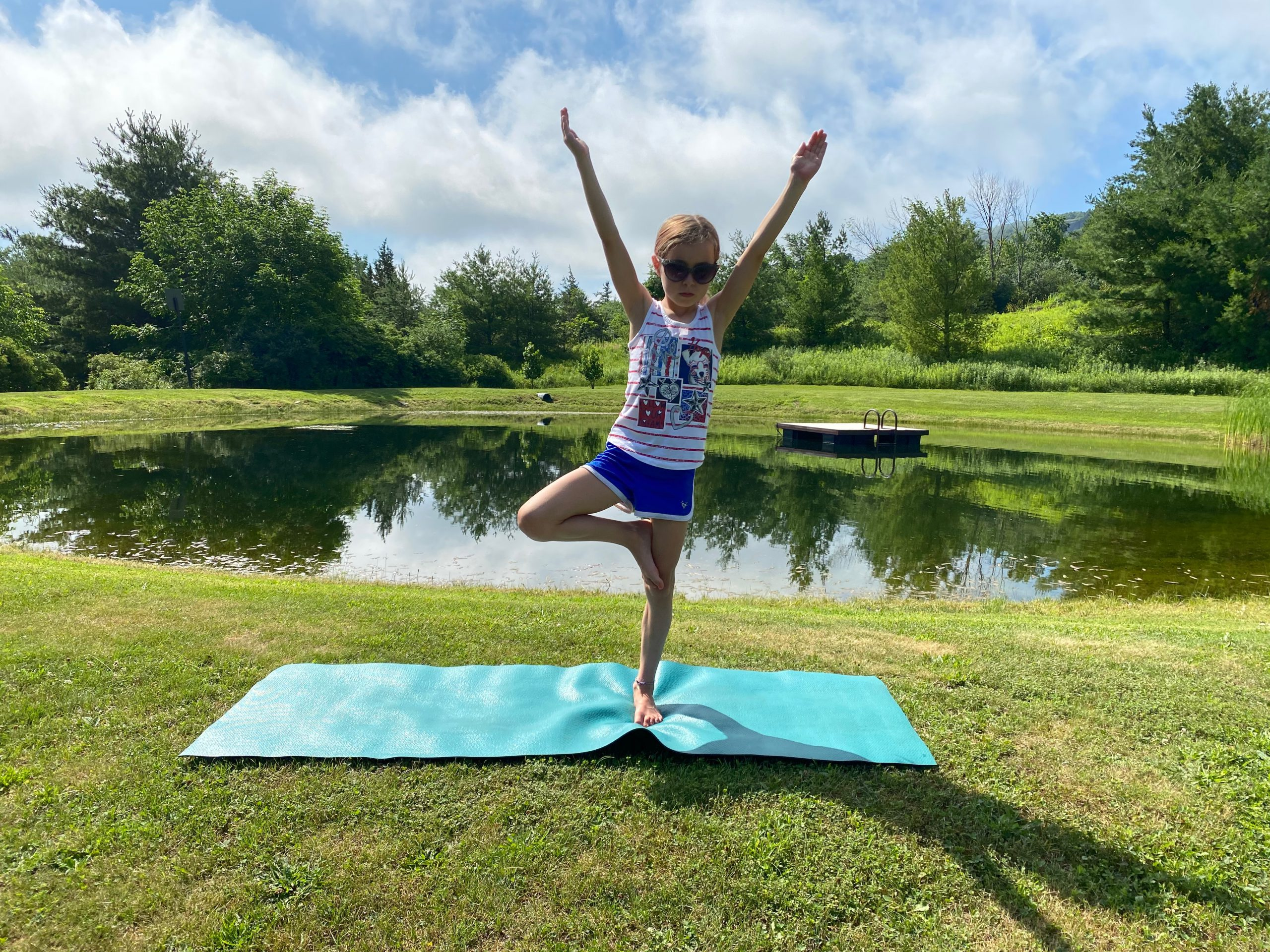 Child stands in tree pose with arms lifted