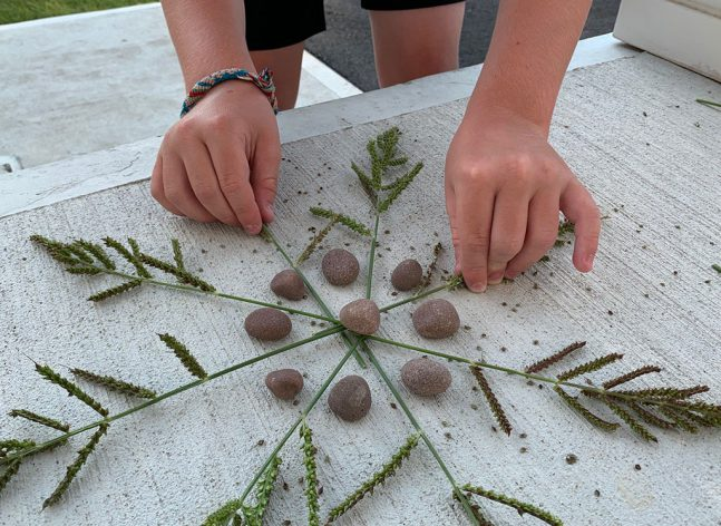 Child's hands creating a Nature Mandala with grass and rocks